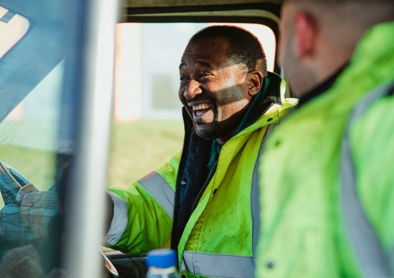Builders in hi vis laughing while driving