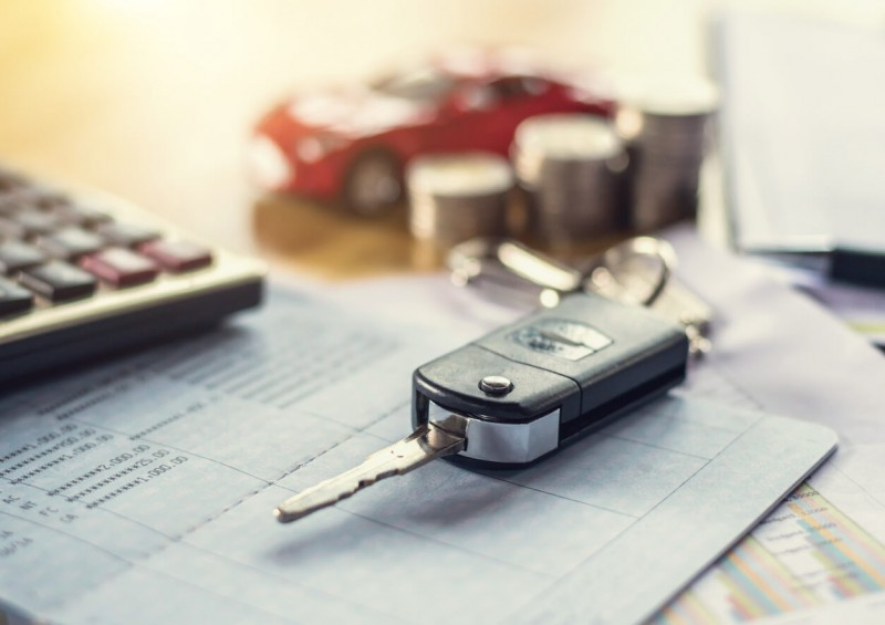 Car keys next to calculator and contract
