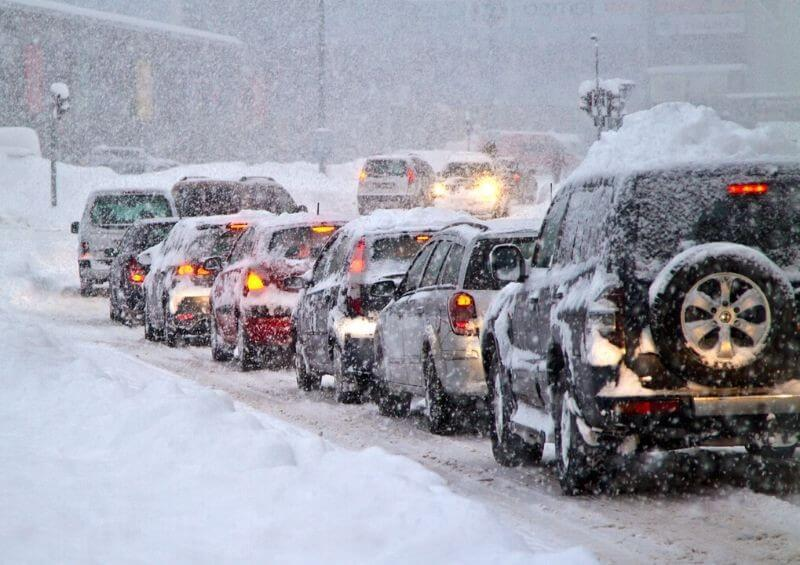 Cars in snow red weather warning traffic