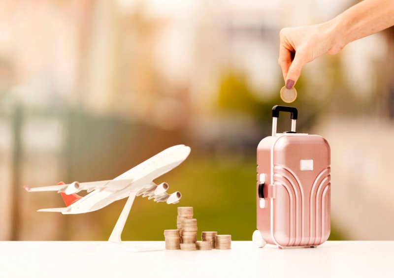 Coins and toy airplane and suitcase