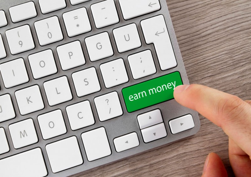 Computer keyboard with green button saying earn money
