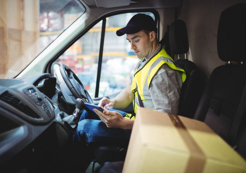 delivery driver in van with package