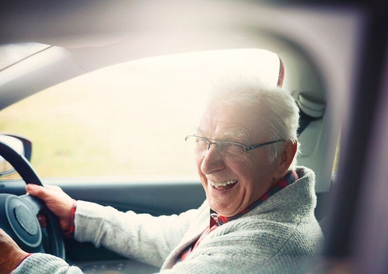 Elderly driver smiling behind the wheel