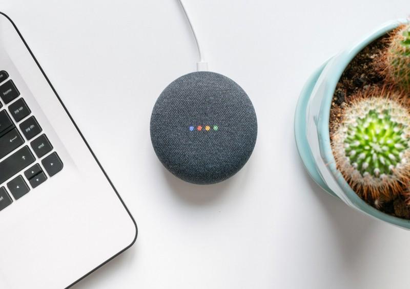 Google Home Mini next to laptop