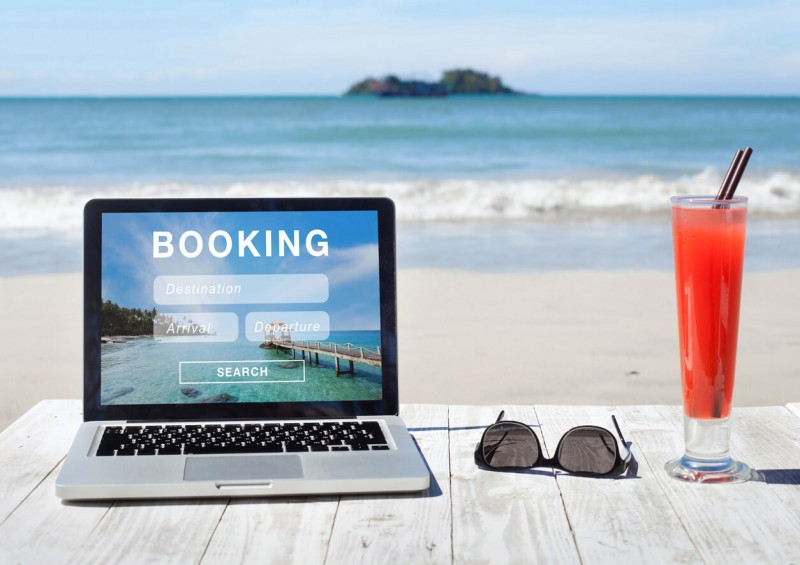 Laptop next to sunglasses and drink on the beach