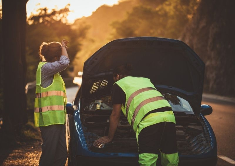 Man helping woman fix car on side of the road
