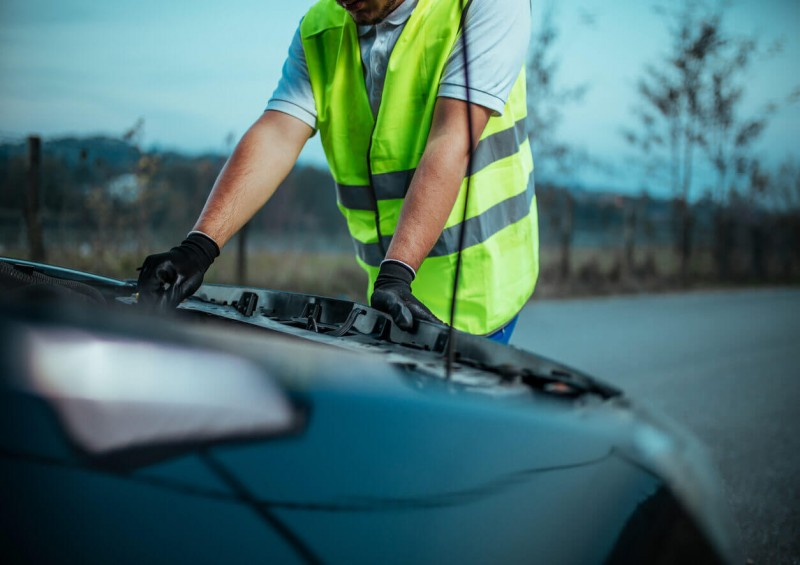 Man in high vis jacket checking car engine