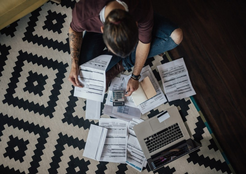 Man on floor sorting out finances