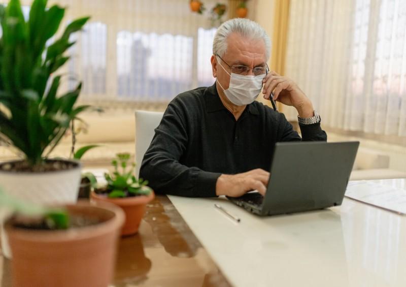Man wearing coronavirus mask checking will online