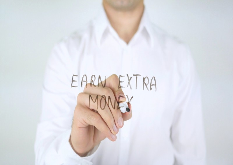 Man writing the words earn extra money on glass
