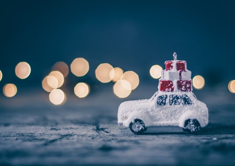 Mini car covered in snow carrying Christmas gifts