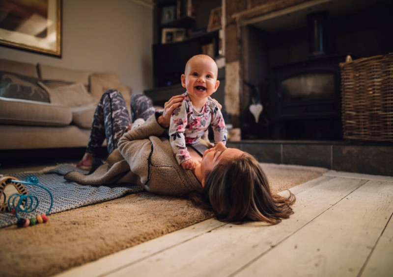 Mother on the living room floor laughing with her baby