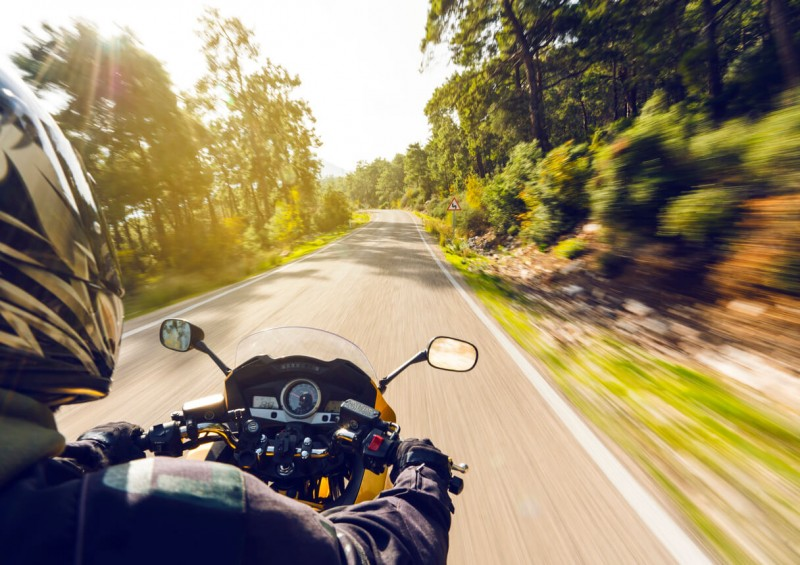 Motorbike going through trees on road