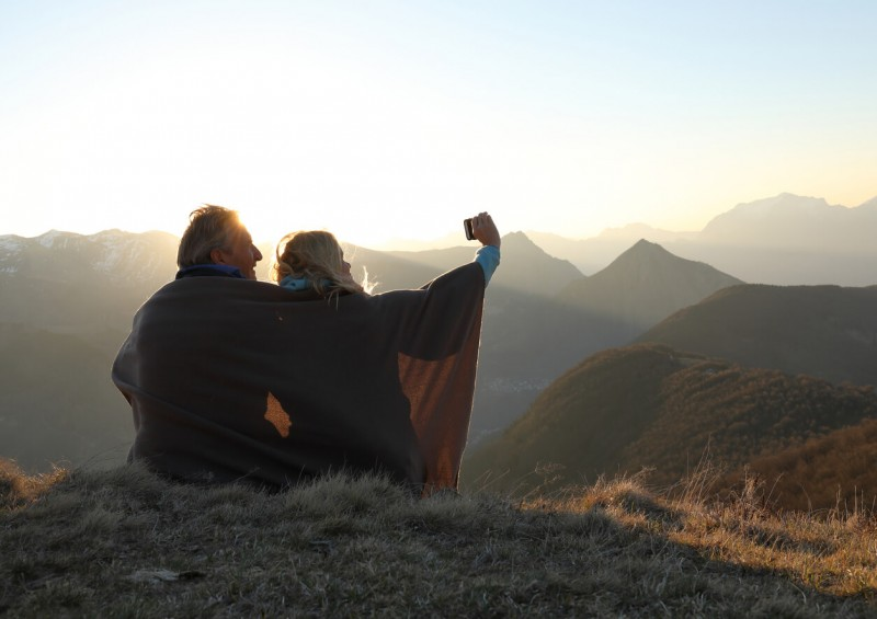Older couple having a selfie at the top of a mountain