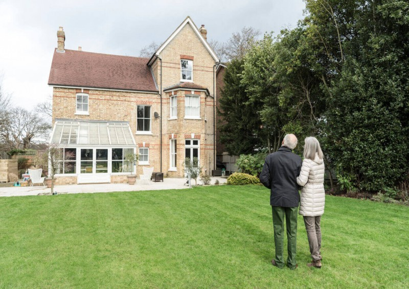 Older couple looking at their home from their garden