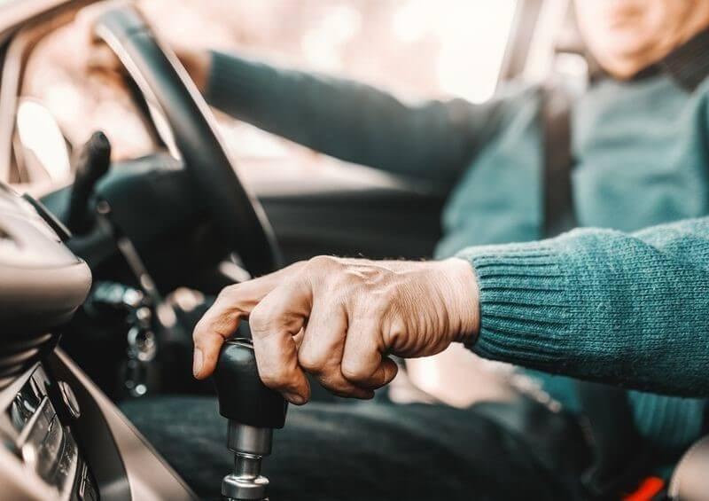 Older gentleman driving car holding gear stick