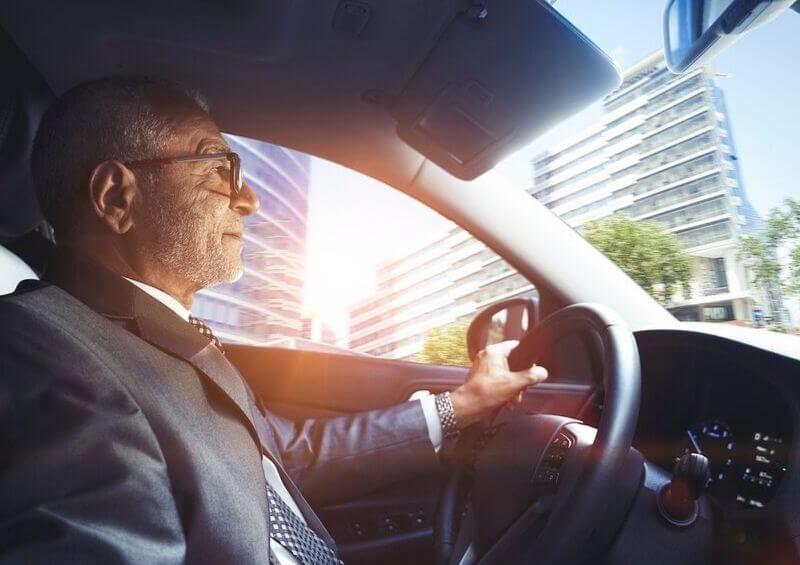 Older man driving through city