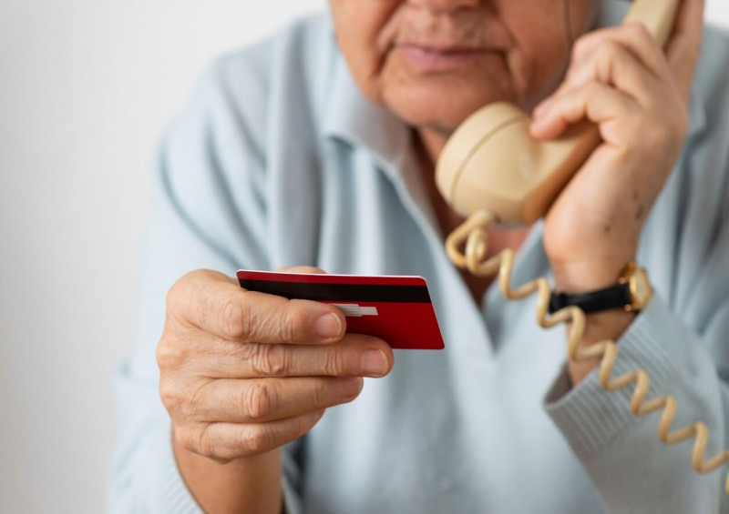 Older man giving bank details to scammer over phone