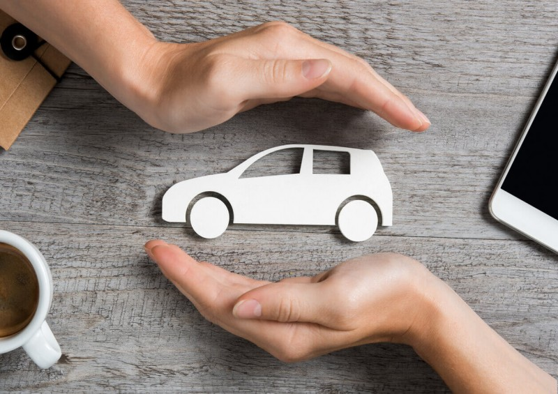 Paper car being protected by two hands