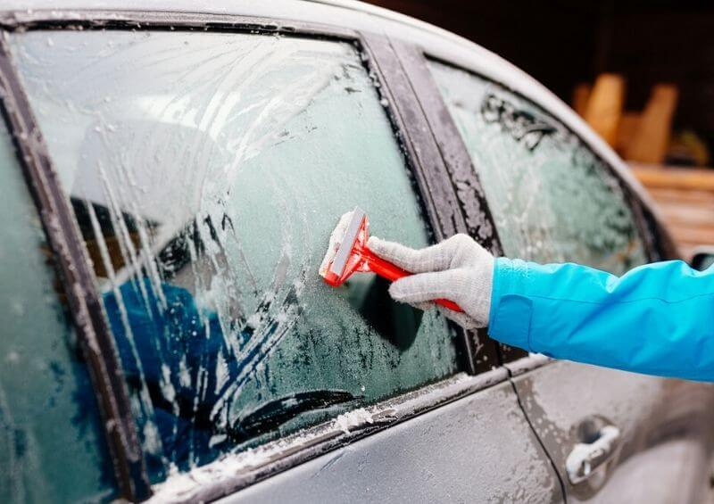 Person de icing their car with an ice scraper during winter