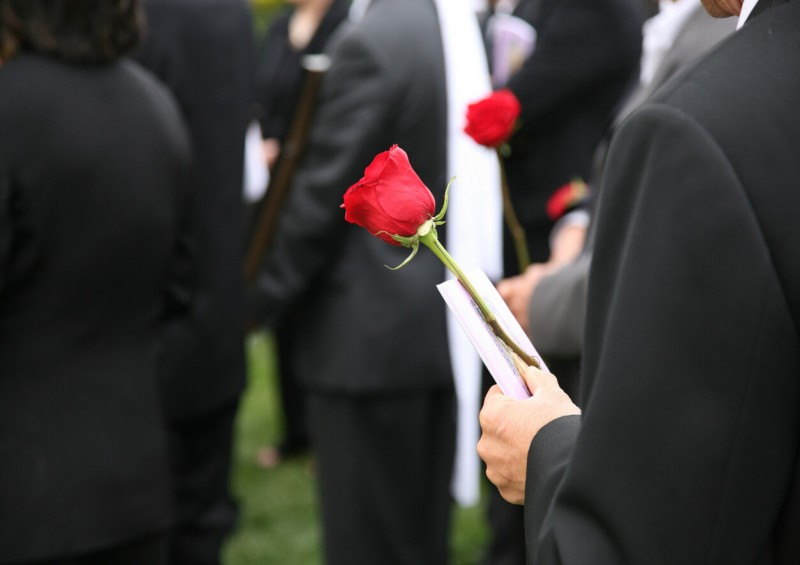Person holding flower at a funeral
