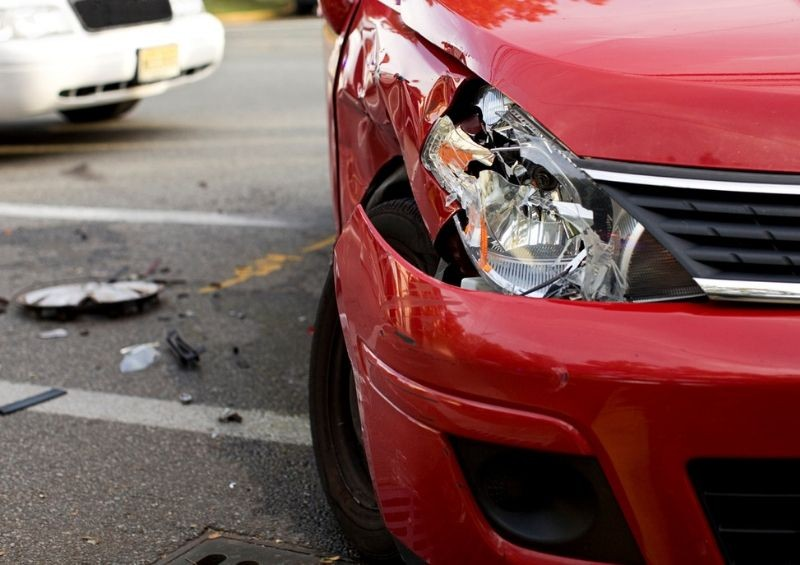 Red car with broken headlight after accident