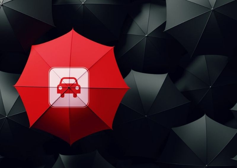 Red umbrella car in the centre surrounded by black ones