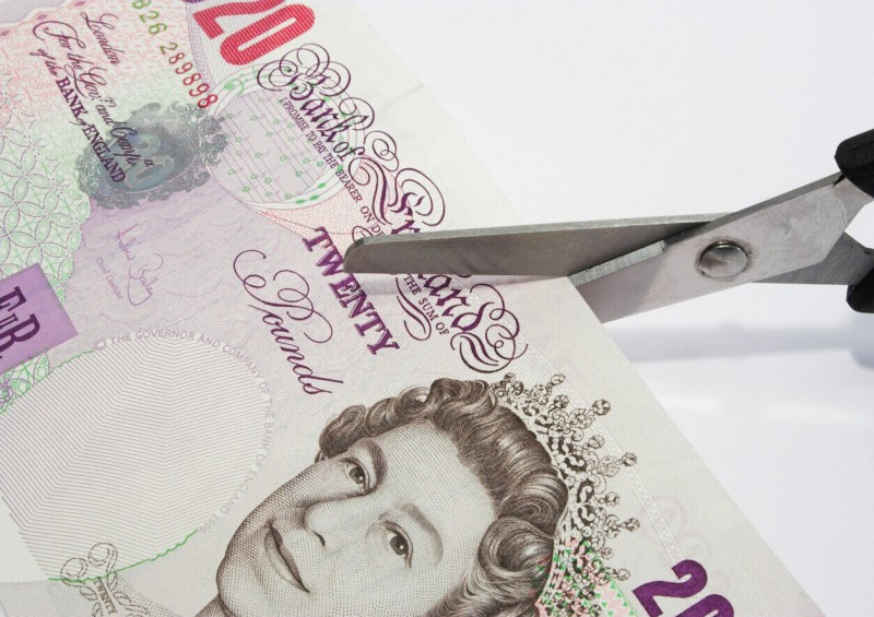 Scissors cutting twenty pound note