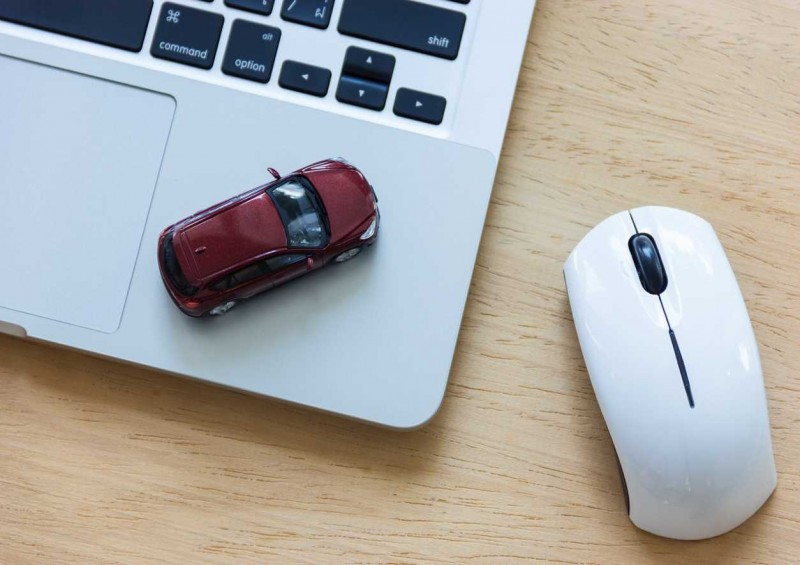 Toy car on laptop while someone gets insurance