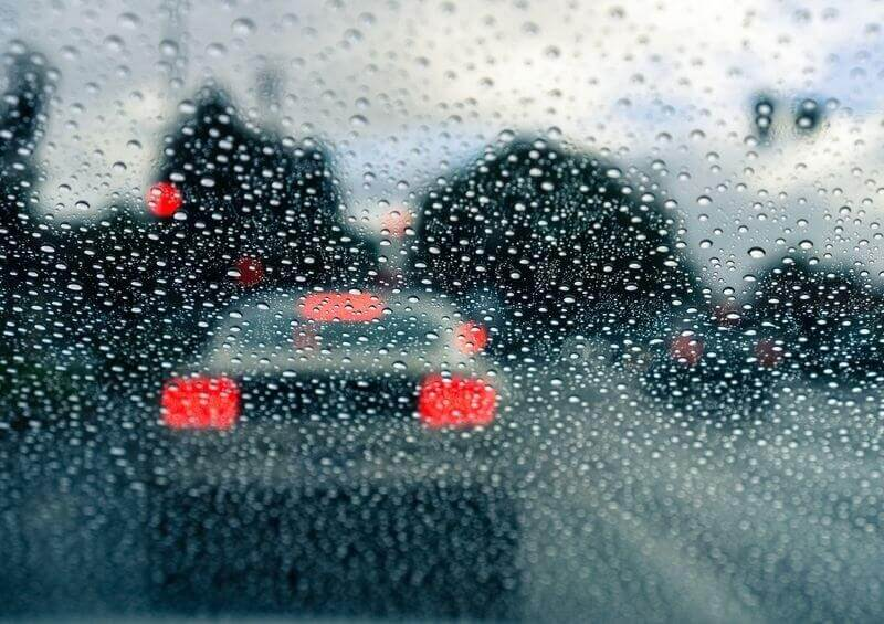 View out of a rainy car windscreen in traffic