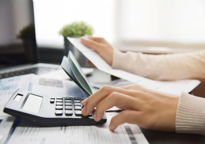 Woman checking her finances with calculator