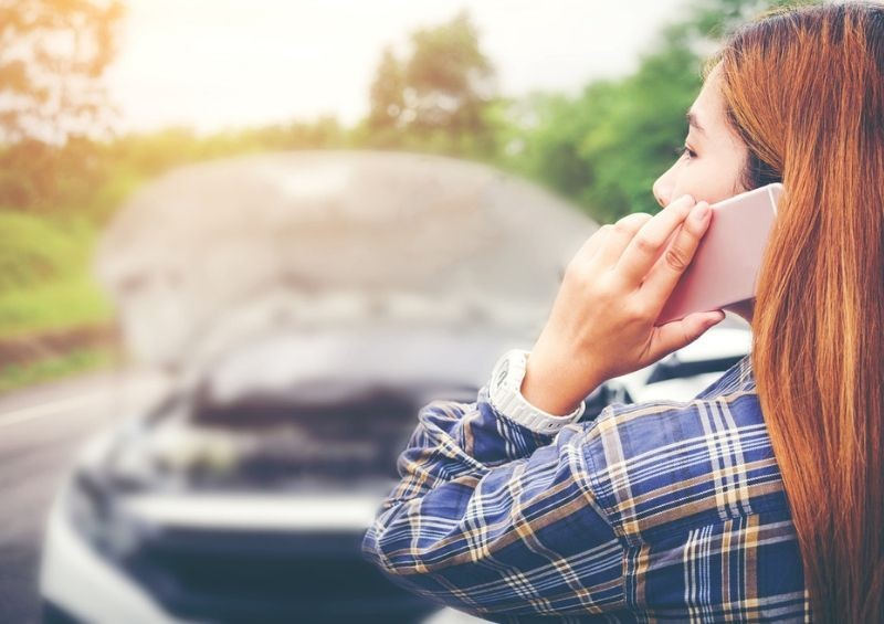 Woman phoning someone after car broken down