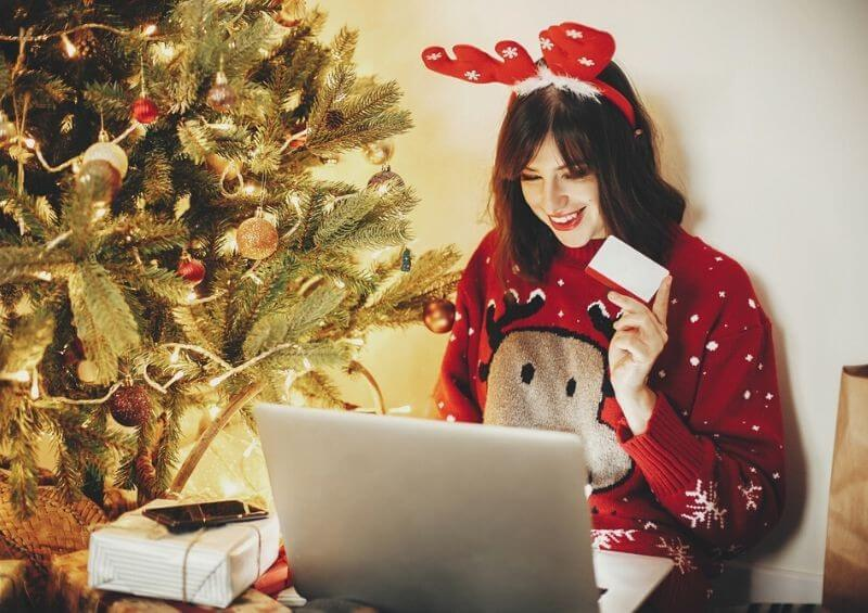 Woman shopping online with Christmas jumper and decorations