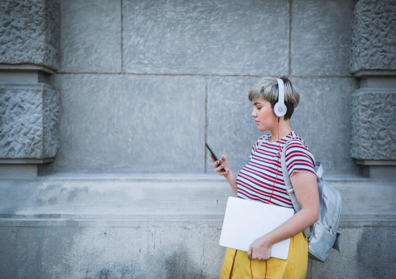 Woman walking outside with gadgets