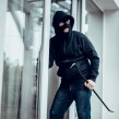 A burglar breaking into a home in the day
