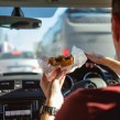A driver eating a burger while driving