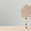 Cardboard cut out of house on top of the word risk