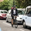 Cyclist driving through cars with mask on