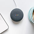 Google Home Mini next to laptop