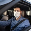 Man driving a car with a face mask on
