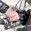 Person putting fuel in car with safety glove on