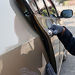 Thief dressed in black hoodie opening car door