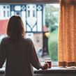 Woman looking out window during Coronavirus quarantine