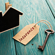 Wooden house with key and insurance tag